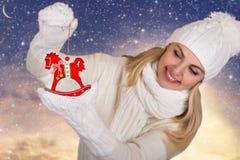Eine junge Frau in schönes Weiß gestrickter Kleidung hält hölzerne Pferdeweihnachtsdekoration für Weihnachtsbaum Frohe Weihnachte lizenzfreies stockfoto