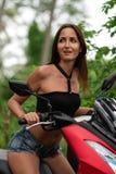 Eine junge Frau schaut weg in der Überraschung und sitzt hinter dem Rad eines Motorrades stockbild
