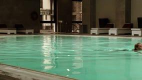 Eine junge Frau schwimmt in einem Pool einer Wellnessmitte stock video