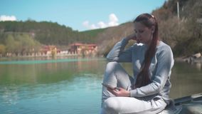 Eine junge Frau sitzt auf einem alten Boot durch den See an einem Frühlingstag und -blicken am Telefon und entspannt sich in der  stock video footage