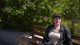 Eine junge Frau sitzt auf einer Bank stock video