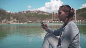 Eine junge Frau sitzt durch den See auf einem Frühlingstag und Blicken in das Telefon, Erholung im Freien Nahaufnahmemädchen stock video