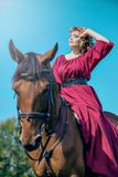 Eine junge Frau sitzt in einem roten Kleid sitzt auf der Rückseite eines braunen Pferds stockbilder
