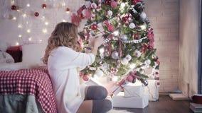 Eine junge Frau sitzt nahe einem Weihnachtsbaum und verziert sie mit Spielwaren stock video
