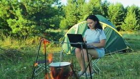 Eine junge Frau sitzt am Zelt und passt den Topf, über dem Feuer zu hängen auf und zu schreiben auf der Laptoptastatur stock video