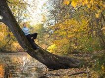 Eine junge Frau steht auf einem Baum und einem Lächeln Stockfoto