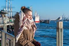 Eine junge Frau steht an einem Pier, der das Wasser betrachtet lizenzfreies stockbild