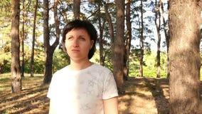 Eine junge Frau steht im Wald und betrachtet die Sonne stock footage
