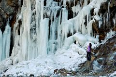 Eine junge Frau steht nahe einem gefrorenen Wasserfall lizenzfreie stockfotografie