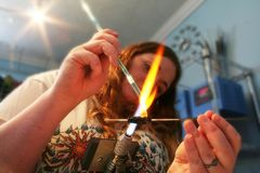 Eine junge Frau stellt Glaskorne mit Hitze her Stockbilder