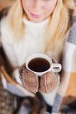Eine junge Frau trinkt ein heißes Getränk im Winter lizenzfreie stockbilder