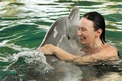 Eine junge Frau umfasst einen Delphin im Pool und schwimmt mit Delphinen lizenzfreie stockfotos