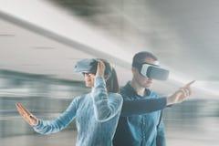 Eine junge Frau und ein junger Mann in den Gläsern der virtuellen Realität Das Konzept von modernen Technologien und von Technolo stockfotos