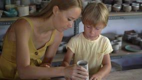 Eine junge Frau und ihr weniger Sohn auf einer Tonwarenvorlagenklasse stock footage