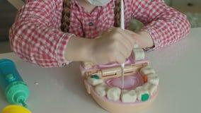 Eine junge Frau und eine Mädchenform ihre Zähne vom Plasticine, fügen ihre Zähne in den Kiefer des Spielzeugs ein, das Mädchen ma stock footage