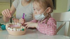 Eine junge Frau und eine Mädchenform ihre Zähne vom Plasticine, fügen ihre Zähne in einen Spielzeugkiefer, ein Mädchen putzt ihre stock footage