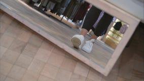 Eine junge Frau versucht an nahe den weißen Turnschuhen des Spiegels im Speicher stock video