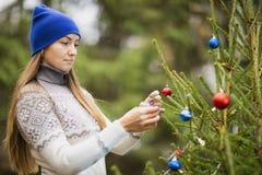 Eine junge Frau verziert den Weihnachtsbaum stockfoto