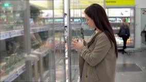 Eine junge Frau wählt und kauft Milchprodukte in einem Supermarkt Glasschaukasten, Jogurt stock footage