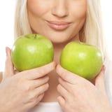 Eine junge Frau, welche die frischen und grünen Äpfel anhält Lizenzfreie Stockbilder