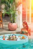 Eine junge Frau wird frühstücken während im Pool tönung ablichtung stockfotografie