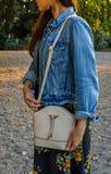 Eine junge Frau, zufällig gekleidet, mit einer Minitasche über ihrer Schulter stockfotografie