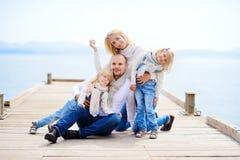 Eine junge, freundliche Familie: Vater, Mutter und zwei Töchter sitzen O lizenzfreies stockbild
