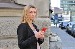 Eine junge Geschäftsfrau, die draußen ein intelligentes Telefon verwendet Stockfotos