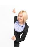 Eine junge Geschäftsfrau, die hinter einer Fahne aufwirft Lizenzfreie Stockfotos