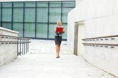 Eine junge Geschäftsfrau, die hinunter die Straße geht Stockfotos