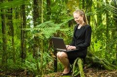 Eine junge Geschäftsfrau, die an ihrem Laptop im Wald arbeitet Lizenzfreies Stockbild