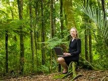 Eine junge Geschäftsfrau, die an ihrem Laptop im Wald arbeitet Stockfotos