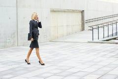 Eine junge Geschäftsfrau geht auf die Straße Lizenzfreies Stockbild