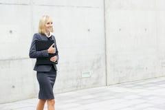 Eine junge Geschäftsfrau geht auf die Straße Stockfoto