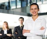 Eine junge Geschäftsfrau vor ihren Kollegen Lizenzfreies Stockfoto