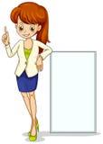Eine junge Geschäftsikone, die neben einem leeren Signage steht Lizenzfreies Stockbild