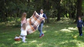 Eine junge glückliche Familie, ein Vati, eine Mutter, eine kleine Tochter und ein Sohn vereinbarten ein Picknick auf einem Hügel  stock video footage