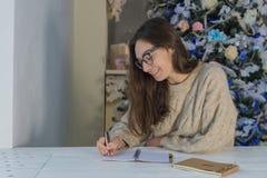 Eine junge glückliche Frau schreibt eine Liste von Weihnachtswünschen nahe bei dem Weihnachtsbaum stockfotos