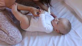Eine junge glückliche Mutter wird mit einem kleinen neugeborenen Sohn mit einer weißen Kamille gespielt stock video