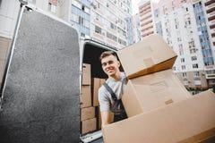 Eine junge hübsche lächelnde tragende Uniform der Arbeitskraft entlädt den Packwagen voll von Kästen Der Wohnblock ist in stockbild