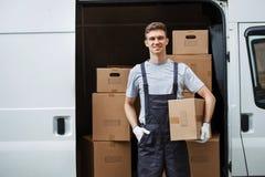 Eine junge hübsche lächelnde tragende Uniform der Arbeitskraft steht nahe bei dem Packwagen voll von den Kästen, die einen Kasten stockbilder