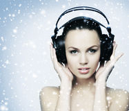 Eine junge Jugendliche, die Musik in den Kopfhörern auf dem Schnee hört Lizenzfreie Stockfotografie