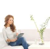 Eine junge kaukasische Frau, die auf einem weißen Sofa sich entspannt Stockbild