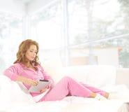 Eine junge kaukasische Frau, die auf einem weißen Sofa sich entspannt lizenzfreies stockfoto