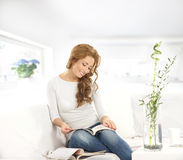 Eine junge kaukasische Frau, die ein Buch auf einem Sofa liest stockbild