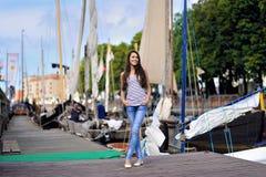 Eine junge lächelnde Frau am frühen Morgen, die auf dem Pier steht Stockfoto