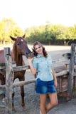 Eine junge lächelnde Frau mit dem gelockten Haar kleidete in den Jeans am Stall mit Pferden an lizenzfreie stockfotos