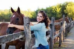 Eine junge lächelnde Frau mit dem gelockten Haar kleidete in den Jeans am Stall mit Pferden an lizenzfreies stockfoto