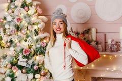 Eine junge lächelnde Frau mit Geschenken einer roten Tasche für Weihnachten lizenzfreie stockfotografie