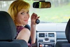 Eine junge lächelnde Frau mit Tasten des Autos Lizenzfreies Stockfoto